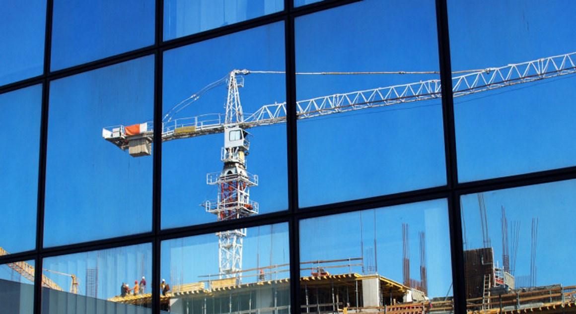 Refleksjonen av en byggekran ses i vinduet til et kontorbygg. Foto.