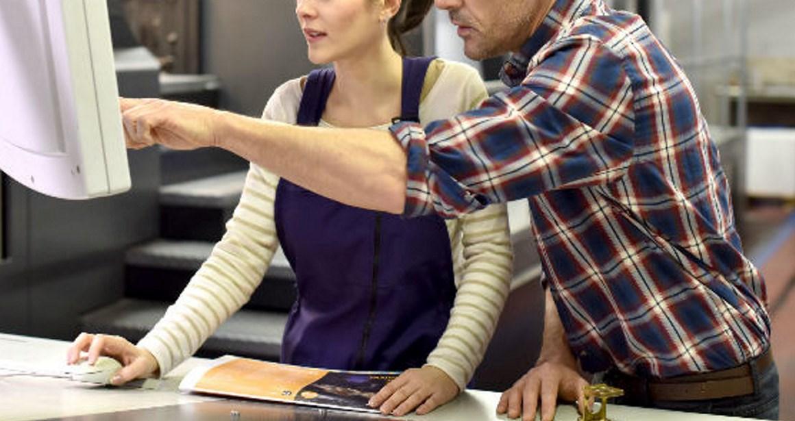 Mann hjelper kvinne på pc. Foto.