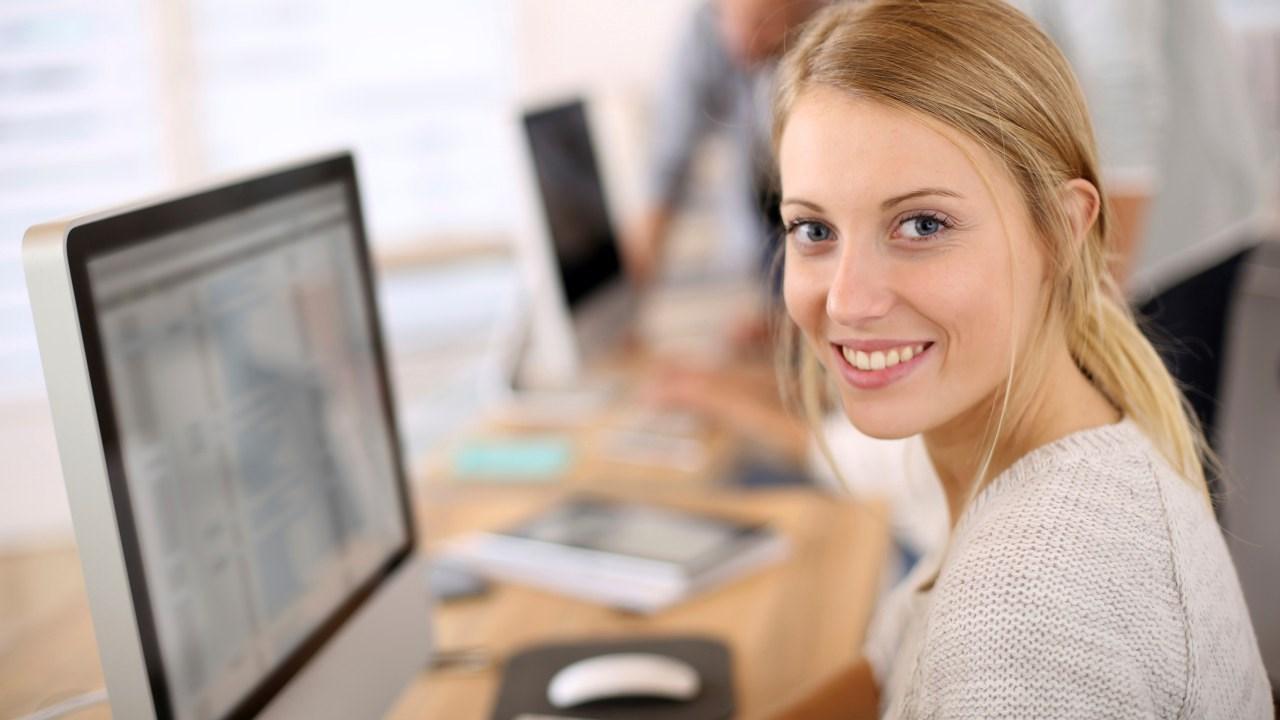 Ung kvinne foran pc-skjerm. Foto.